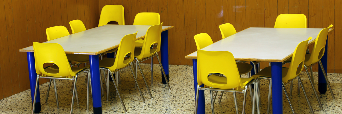 Empty tables and chairs in a children's classroom | Sparkhouse Blog