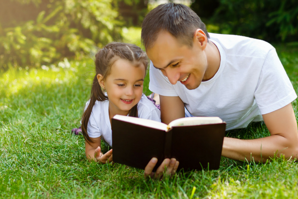 A young girl and man read the Bible together | Sparkhouse Blog