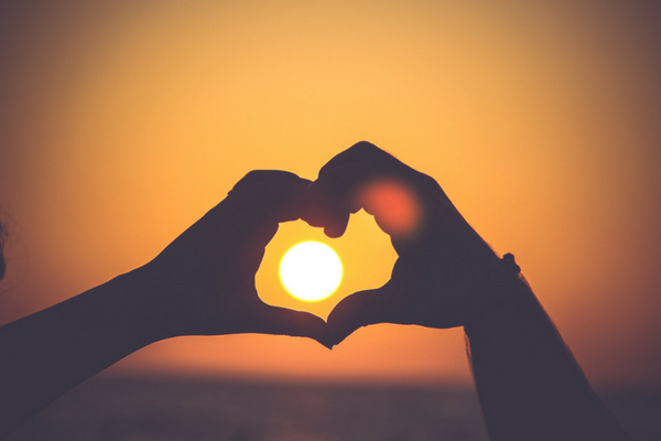 Two hands make a heart around a sun | Sparkhouse Blog