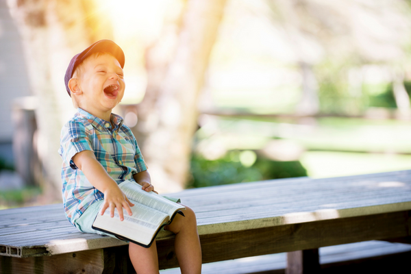 Kid smiles while reading a Bible | Sparkhouse Blog