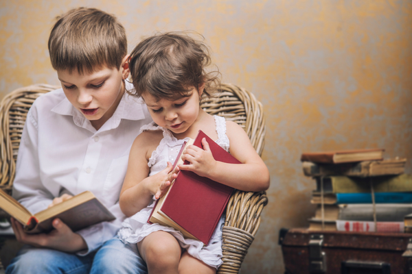 Older kid reads to younger kid | Sparkhouse Blog