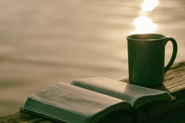 Photo of a Bible, coffee, and the sun shining—perfect for quiet Holy Week reflection | Sparkhouse Blog
