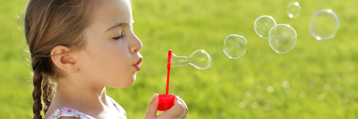 Young girl blows bubbles | Sparkhouse Blog