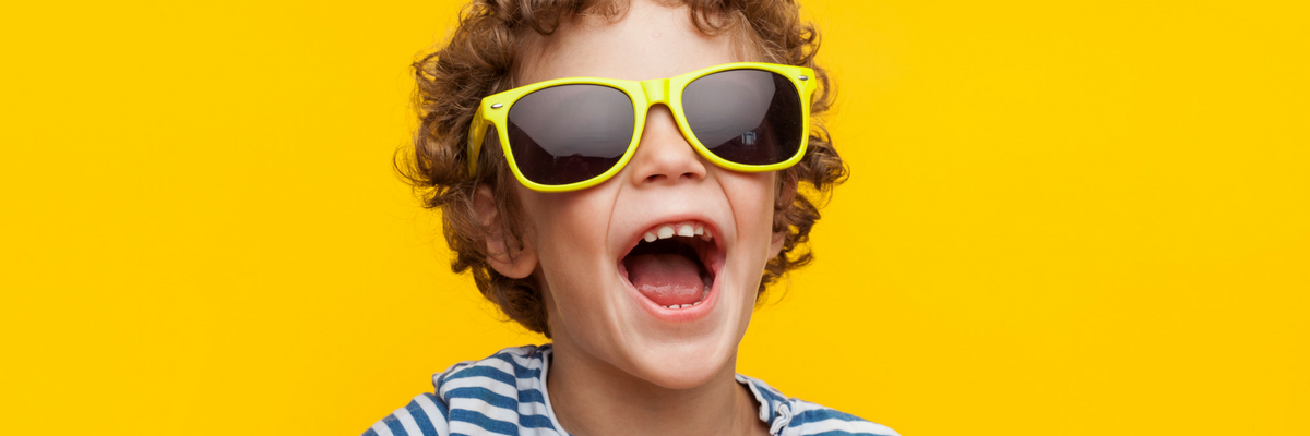 Kid wearing sunglasses laughs in front of summery yellow background | Sparkhouse Blog