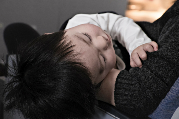 Baby sleeps in caregiver's arms | Sparkhouse Blog