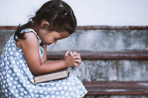 A little girl prays in her Sunday dress | Sparkhouse Blog