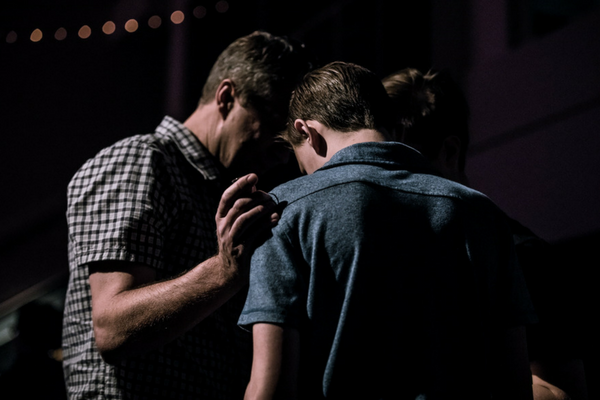 Three people huddle in prayer | Sparkhouse Blog