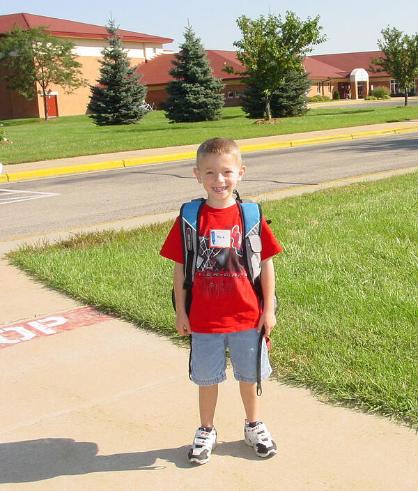 A kindergartener standing outside wearing a backpack